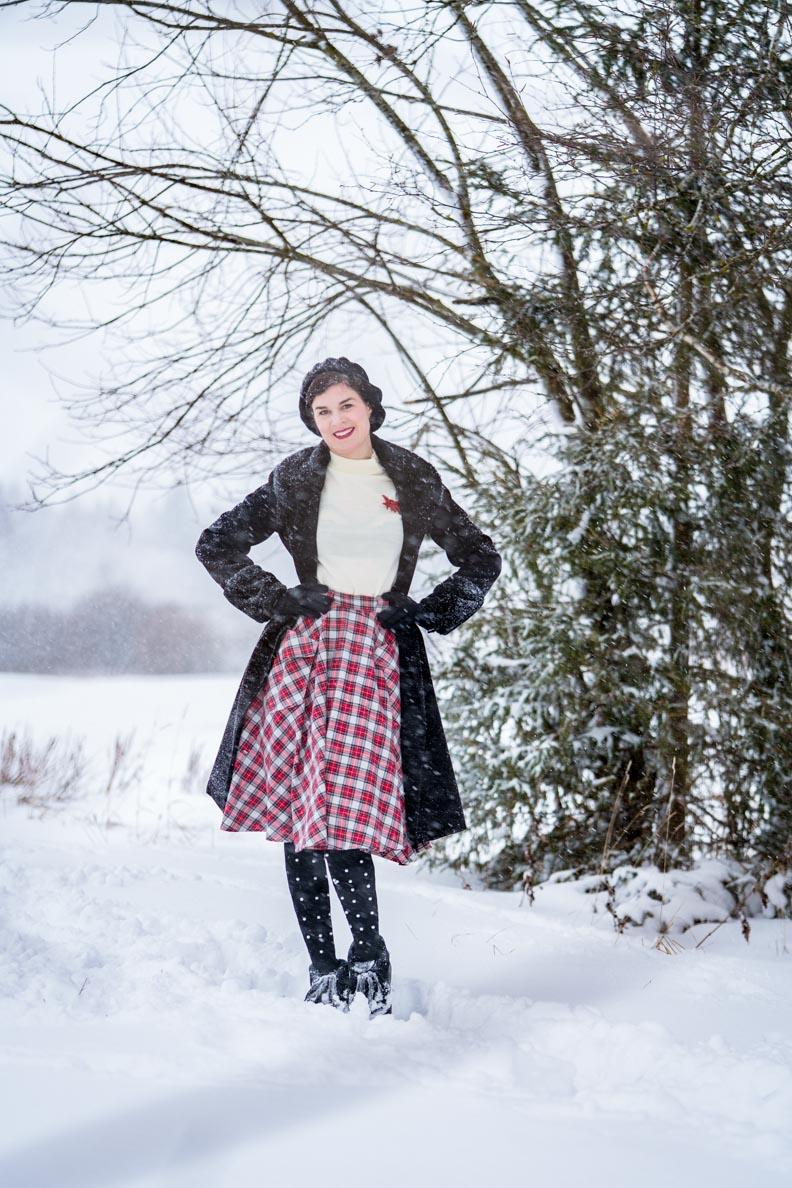 Elegante Winter-Outfits: RetroCat mit Rollkragenpullover, Retro-Mantel und Rock im Schnee