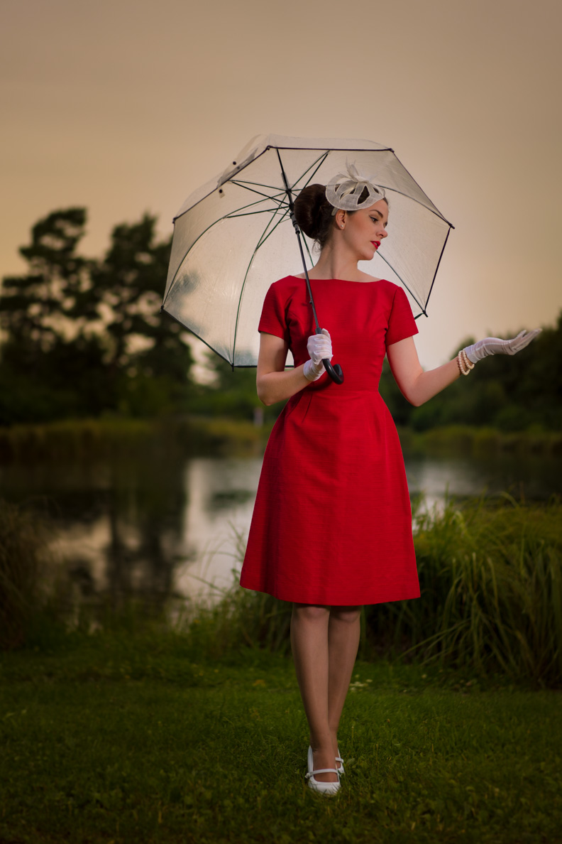 RetroCat mit einem roten Vintage-Kleid sowie weißen Retro-Accessoires im Regen
