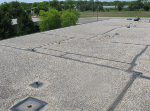 PHOTO 1: This EPDM roof's service has been extended for nine years and counting, approaching 30 years in-situ performance. Here, the restoration of perimeter gravel-stop flashing and lap seams, as well as detailing of roof drains, penetrations and roof curbs, is nearing completion.