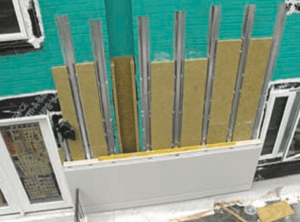 Insulated metal panels (IMPs) were attached to the existing brick fac?ade during the Castle Square DER. Note the mineral wool added in the cavity between the IMPs and existing brick. This system was designed with analysis from a building-science professional. Even with scalable repeatable models, each building will have its own set of unique prop- erties that require building-science analysis and recommended design solutions. PHOTO: Kingspan