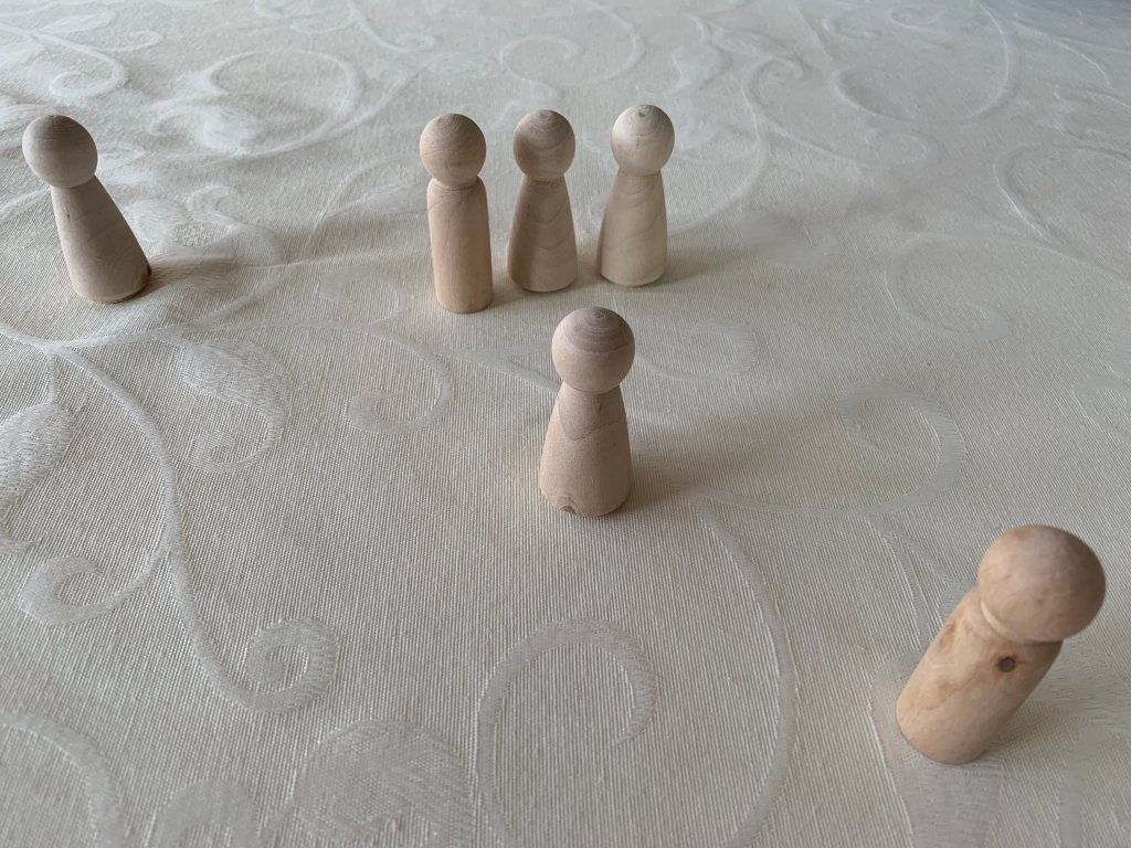 A picture of small wooden dolls representing various family members. The family constellation methodology can help you look at the impact of family on health and illness and gain new perspectives.