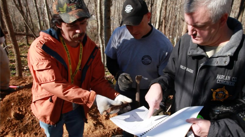 Todd Matthews (left), a Kentucky state trooper (center) and Harlan County Coroner Philip Bianchi compare a bone found at Mountain Jane Doe's exhumation site in Harlan with an example in a forensic manual.
