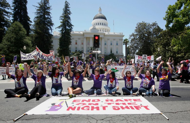 Protesters hold hands as they block the street outside the Capitol during a demonstration in support of a measure aimed at protecting women custodial workers, Tuesday, May 31, 2016, in Sacramento, Calif. Hundreds rallied in support of a bill, AB1978, by Assemblywoman Lorena Gonzalez, D-San Diego, to protect female workers in janitorial positions from sexual harassment and assault in the workplace.