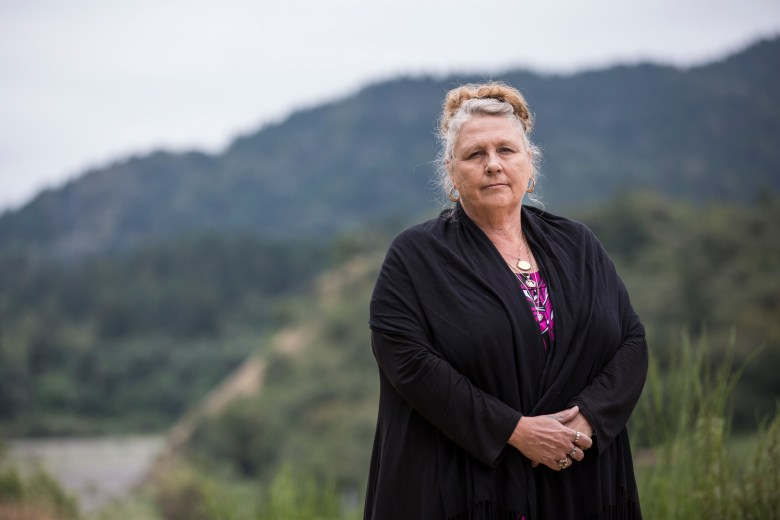 """Debra Carey, a human rights activist and volunteer who helps immigrants, the homeless and seasonal workers in need, poses for a portrait near a homeless encampment she helped secure for those in need nicknamed """"Hippie Hill,"""" in her home town, Garberville, CA, on May 13, 2016."""
