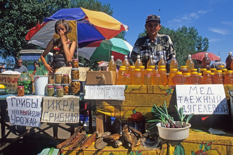 SROSTKI, SIBERIA, RUSSIA - JULY 12: Med and bee honey for sale at farmers market on July 12, 2004 in Srostki, Siberia, Russia. Farmers markets are very popular in new Russia.