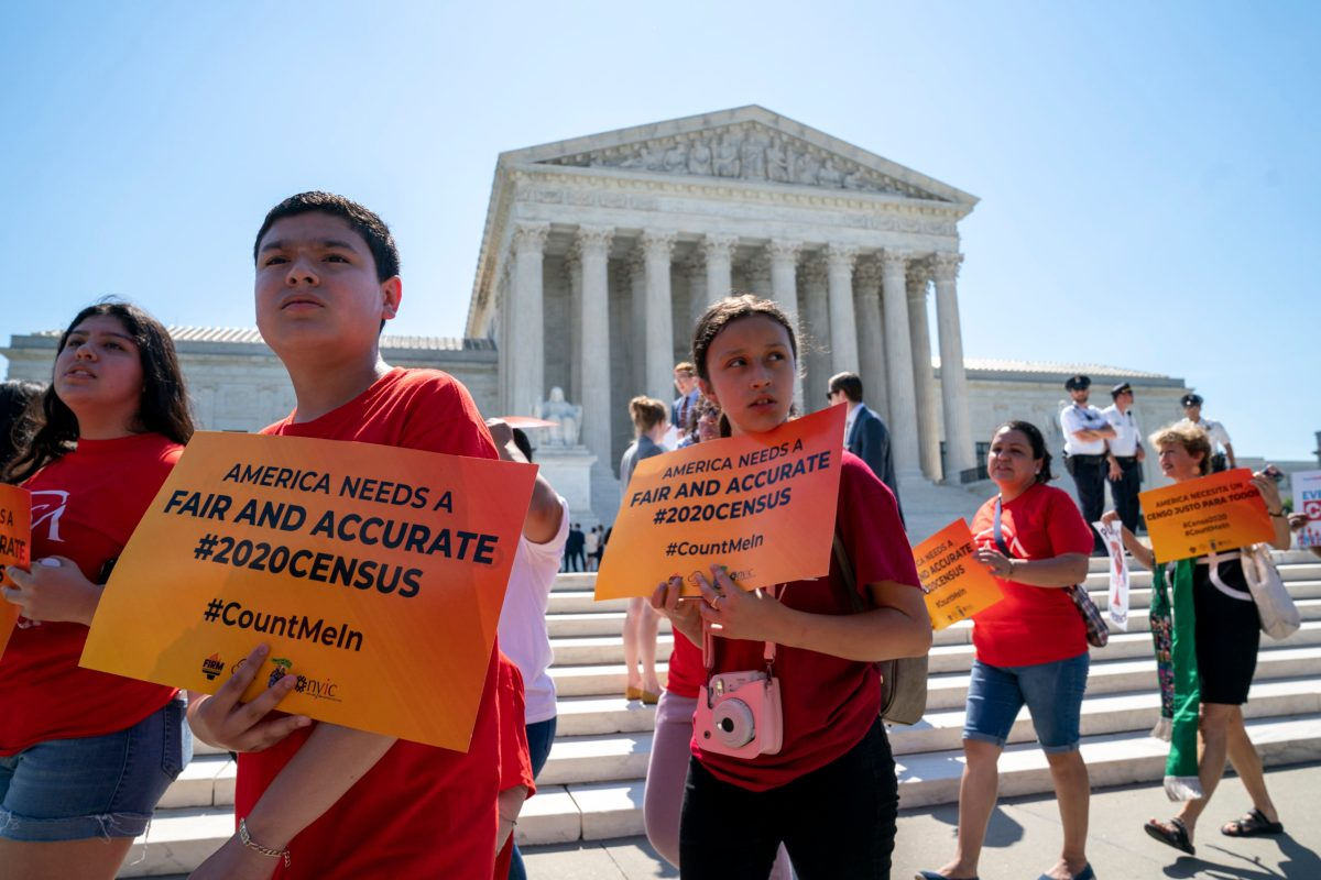 "A group of young demonstrators walk outside the Supreme Court, holding signs that say ""America needs a fair and accurate #2020Census"""
