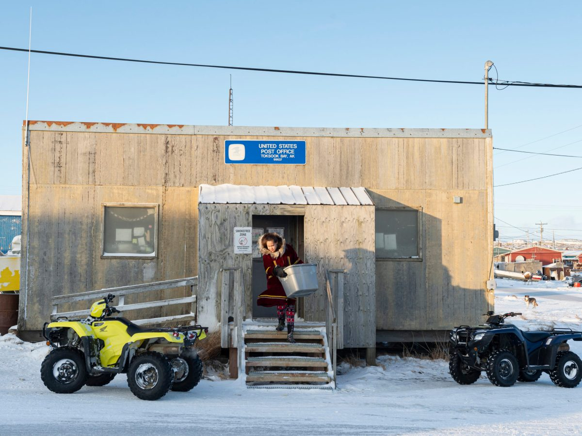 A woman carries a box out of the post office in the wintry landscape of Toksook Bay.