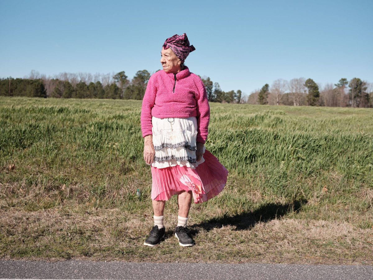 A portrait of Doña Amalia, who is wearing a pink fleece jacket and a pink and white skirt, as well as tennis shoes. She stands in front of a field of tall grass.