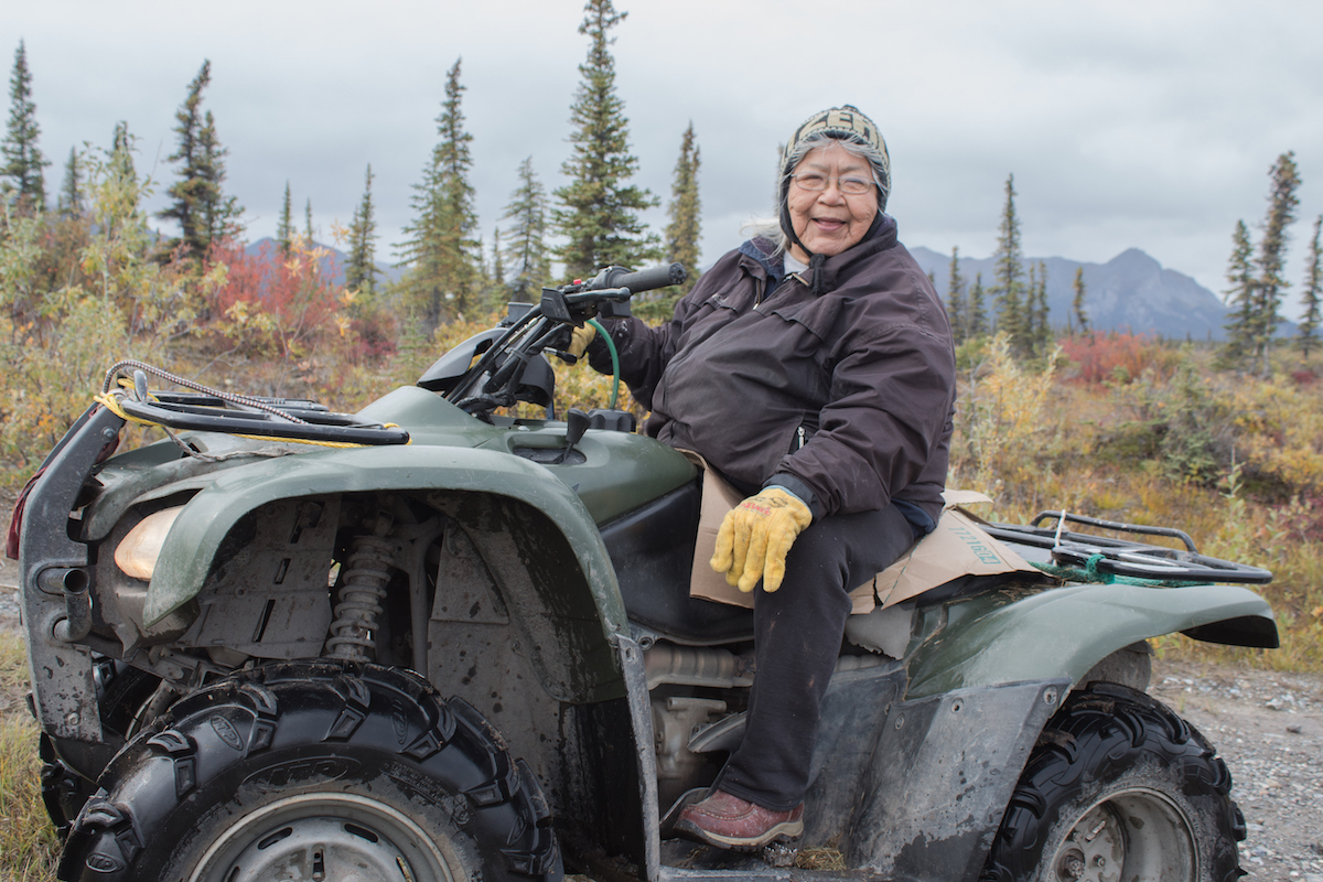 Sarah James, in a winter coat, hats, and work gloves, sits astride a four-wheeled vehicle in front of pine trees and a mountain.