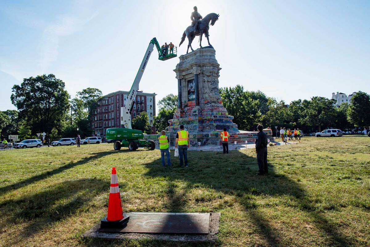 Workers on an aerial work platform examine a statue of Robert E. Lee. Other workers in safety vests stand around its base.
