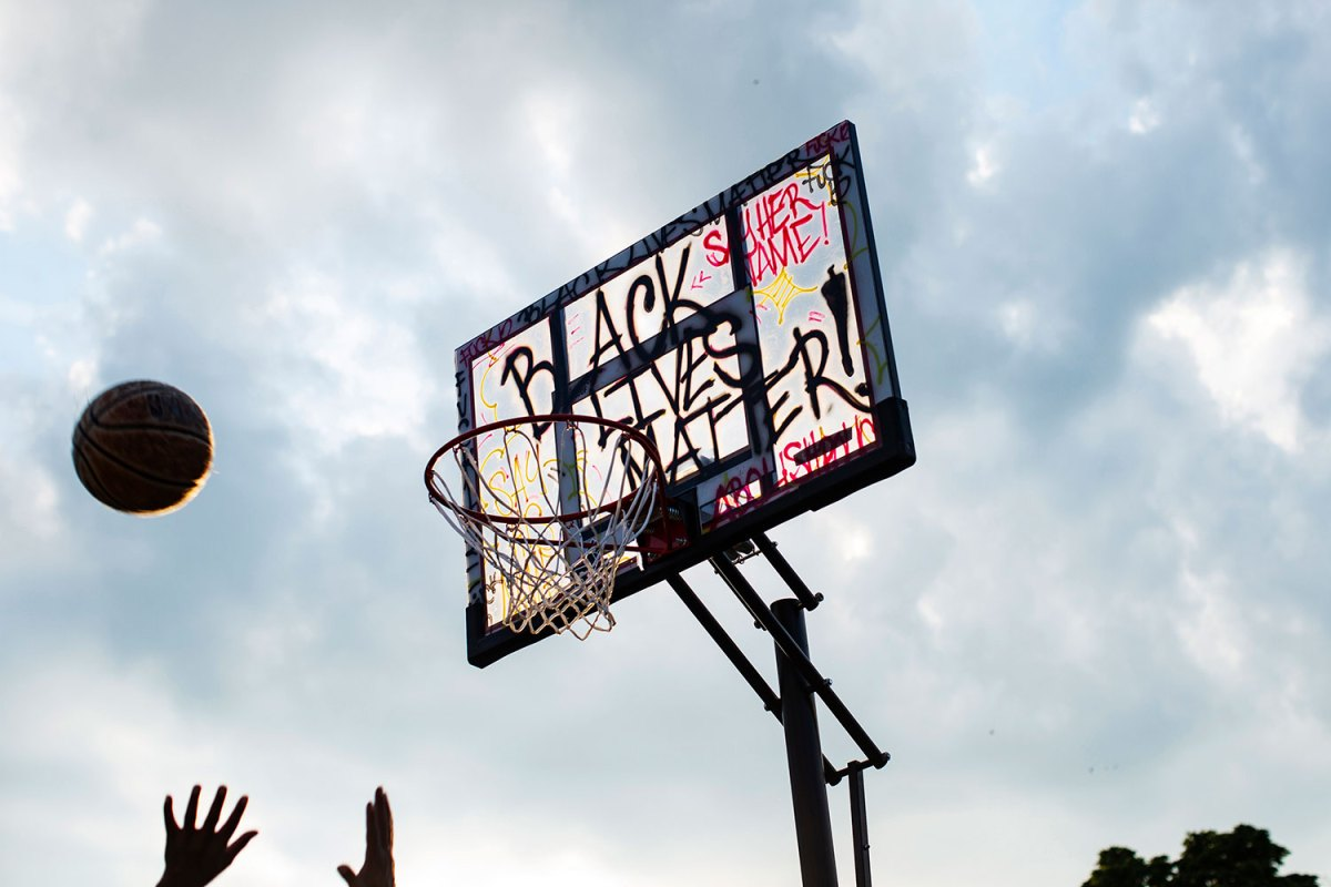 """A large portable basketball hoop, tagged with """"Black Lives Matter"""" and other graffiti, is silhouetted against the sky."""