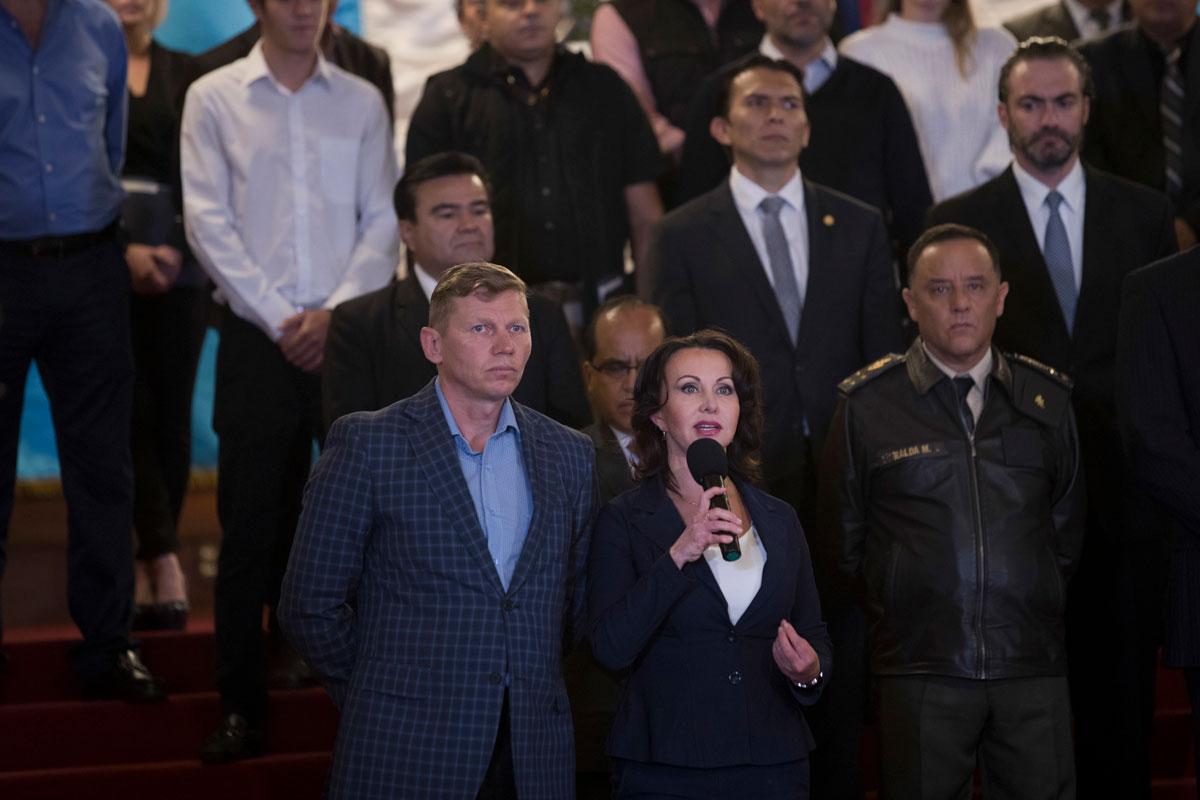 Irina Bitkova holds a microphone. Her husband, Igor Bitkov, stands beside her.