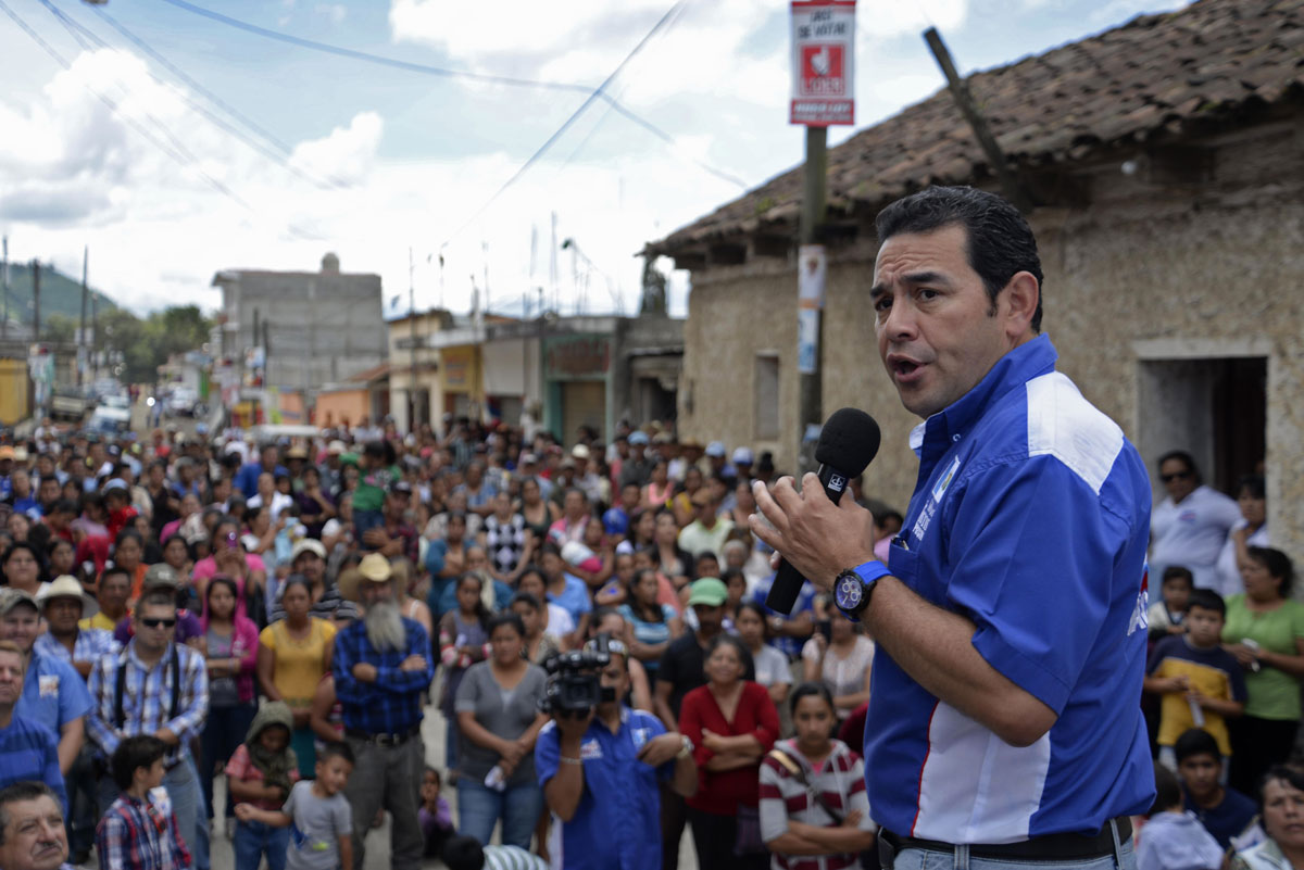 Guatemalan presidential candidate Jimmy Morales stands before a crowd gathered on a street, holding a microphone.