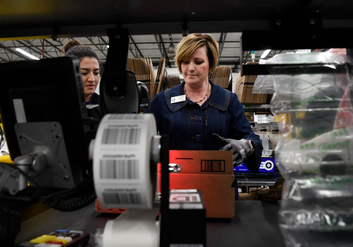 Looking through a shelf of packing supplies, two women package an Amazon order.