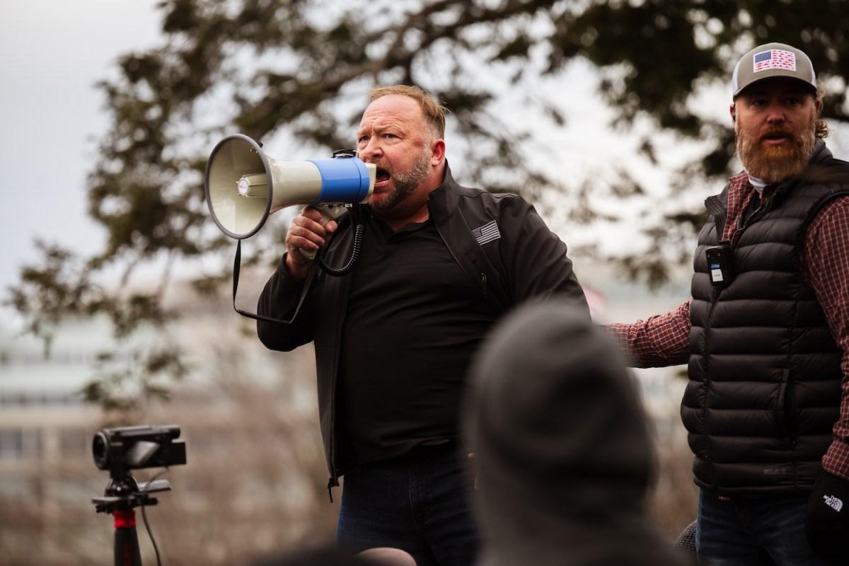 Alex Jones speaks into a bullhorn.