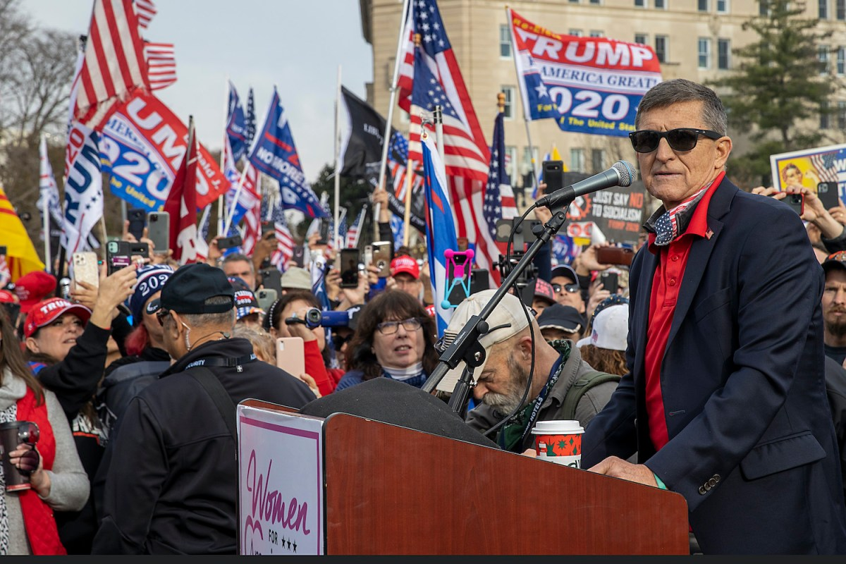 Michael Flynn stands at a podium. Behind him is a crowd of people waving American flags and Trump campaign flags.
