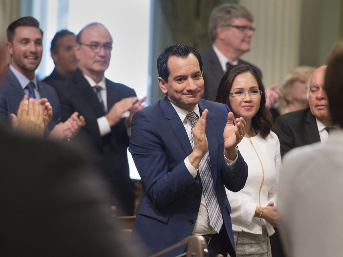 Anthony Rendon stands among other legislators in the California Assembly chambers as they applaud.