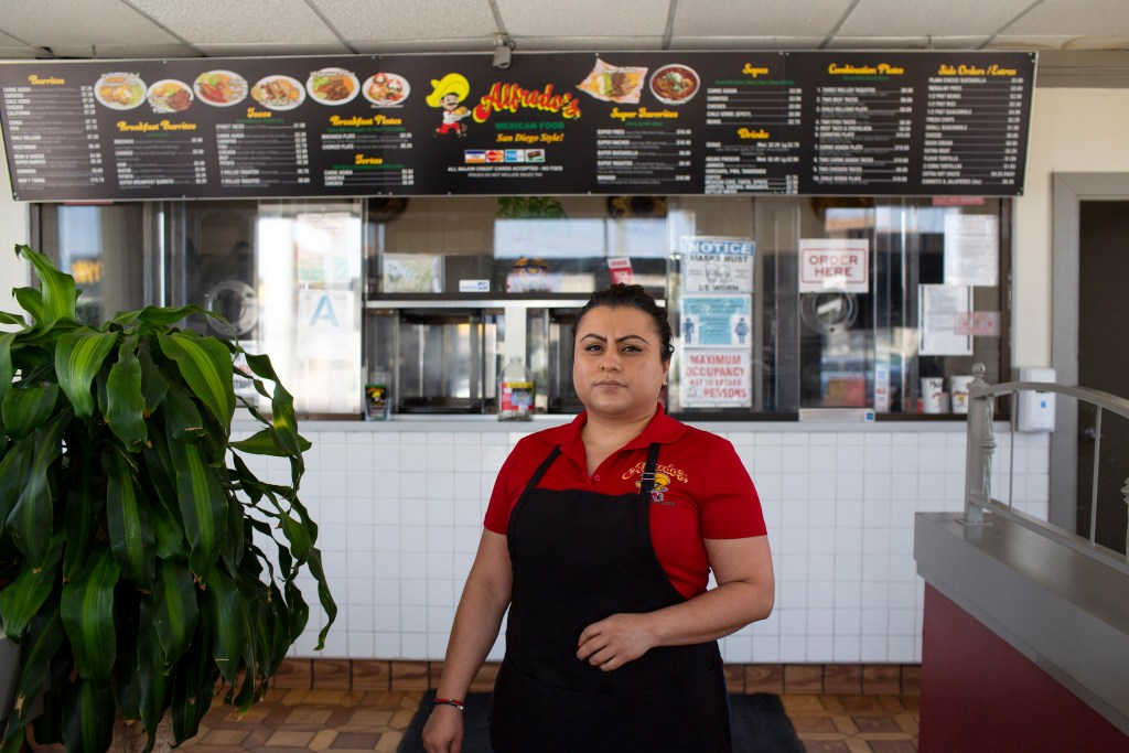 Herminia Reyes stands inside her restaurant. Behind her, a menu board hangs above the walk-up order counter.