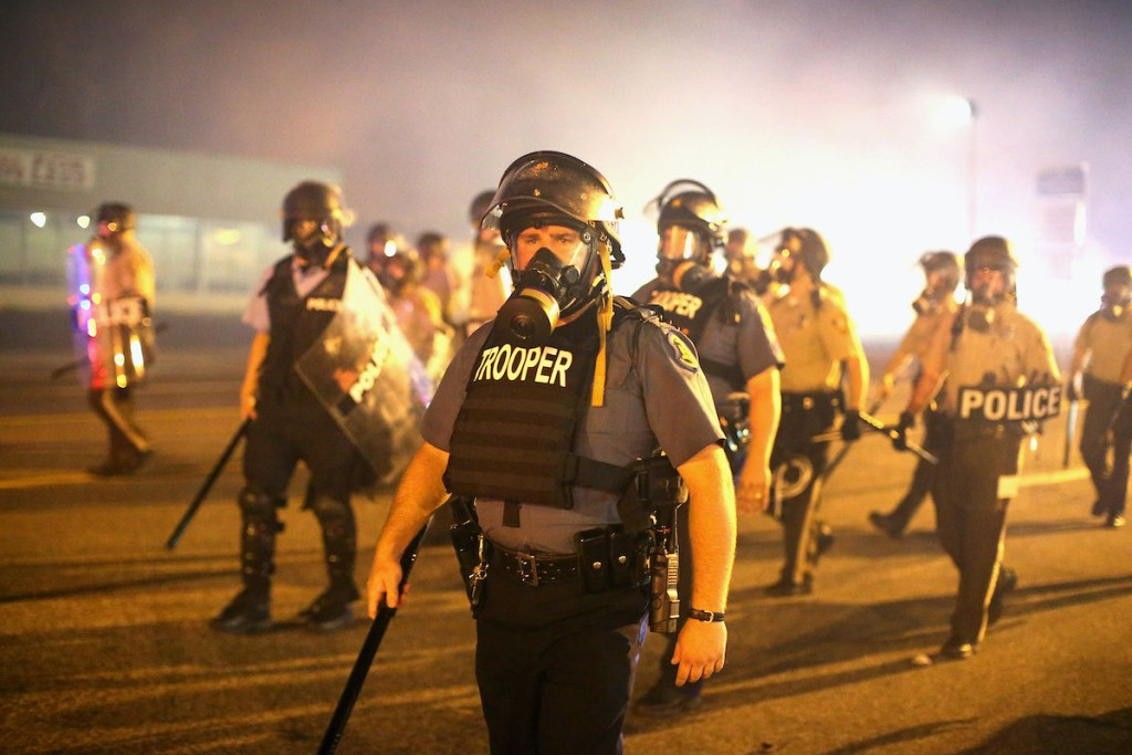 A group of officers are dressed in riot gear, including gas masks. Many carry shields and clubs. The air is hazy with tear gas.