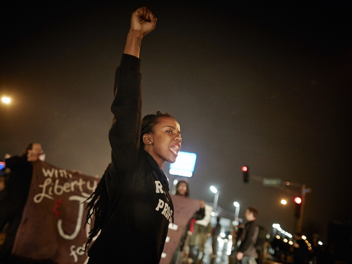 Brittany Ferrell raises her right first in the air while shouting. Behind her, two people hold a large banner.