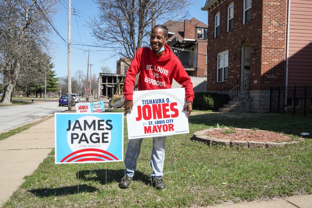 "Rasheen Aldridge places a yard sign that reads: ""Tishaura O. Jones for St. Louis City Mayor."