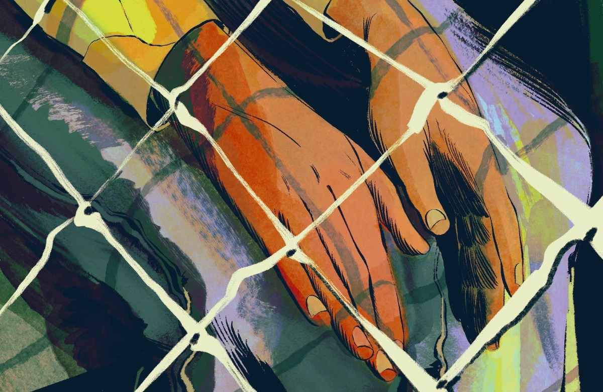 A child's hands are shown resting in the child's lap. The child is behind a chain-link fence.