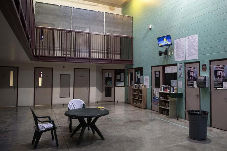 A two-story common room contains doors to several detention rooms. The common room has a small table, two chairs, a few bookcases and a large trash can. A small TV is mounted high on the wall.