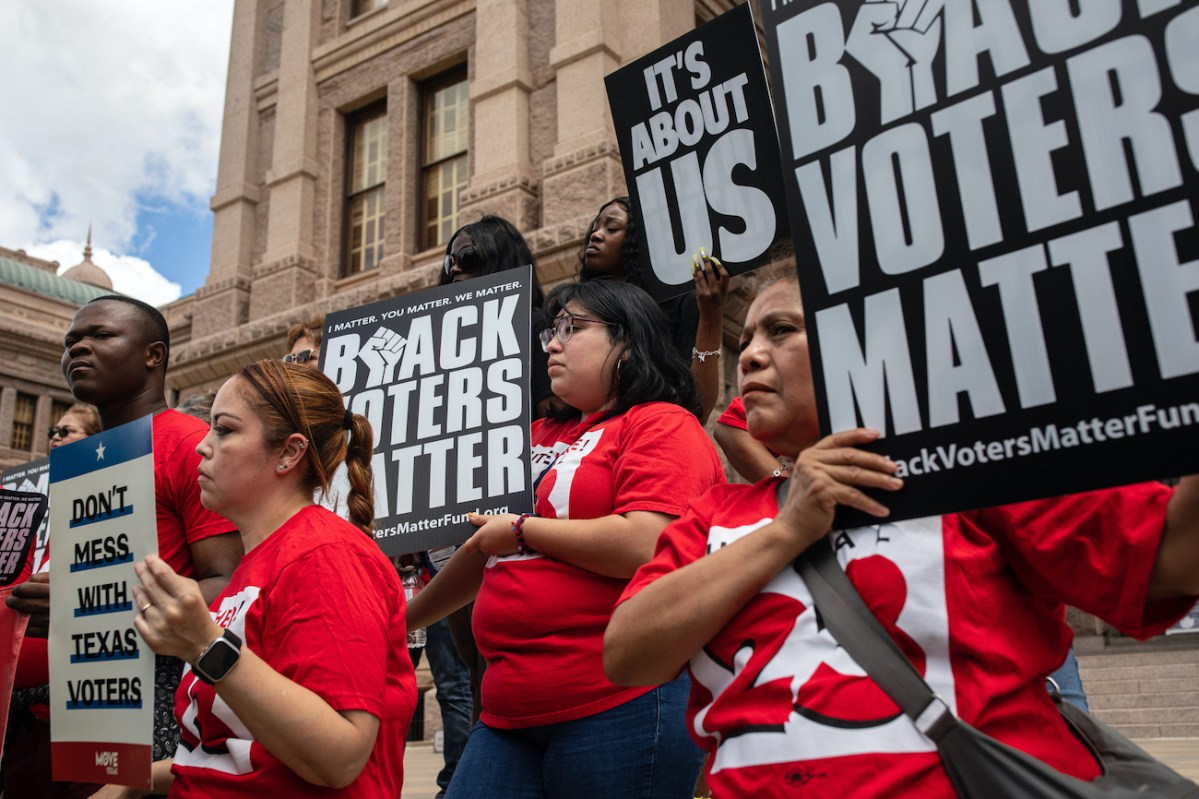 """Protestors in matching red T-shirts stand on the steps of the Texas Capitol. They hold signs that read: """"Don't mess with Texas voters,"""" """"Black voters matter"""" and """"It's about us."""""""