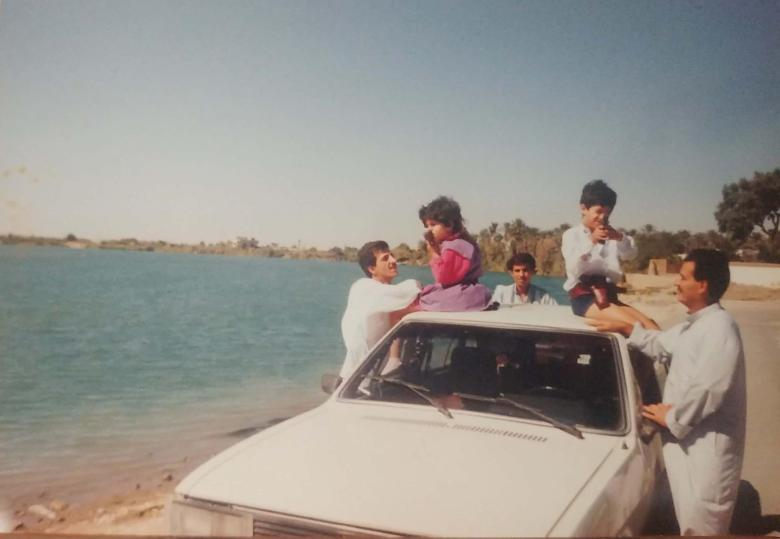 Feurat Alani and his sister sit atop a car parked on the banks of a river. Three uncles stand around them.