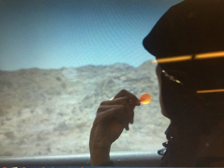A woman looks out a car window as desert landscape passes by. She holds a small orange lollipop.