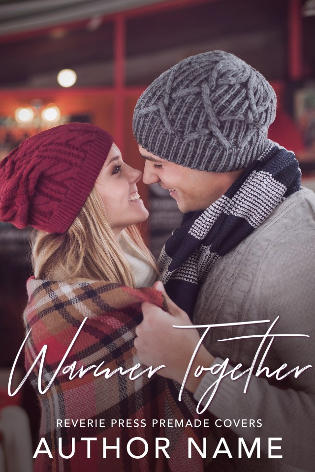 An image of a couple dressed in warm layers for winter - the man is pulling a blanket around the woman's shoulder while they look as if they might kiss