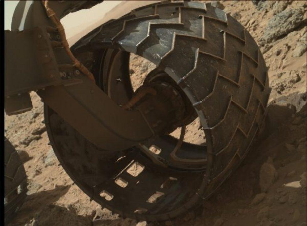 La roue avant gauche de Curiosity rover de la NASA montre des bosses et des trous dans cette image prise lors de la 469e jour martien (30/11/2013). L'image a été prise par l'Imager Mahli qui est monté à l'extrémité du bras robotisé de Curiosity. Curiosité avait alors roulé 4,47 km (source NASA/JPL-Caltech)