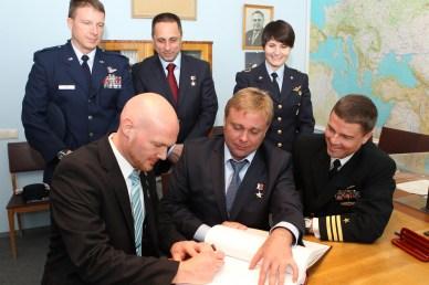 Au Centre de formation des cosmonautes Gagarine à Star City en Russie, Alexander Gerst de l'Expedition 40/41 signe un livre de cérémonie à coté de ses coéquipiers. A l'arrière, l'équipage de secours (source Astro_Alex)