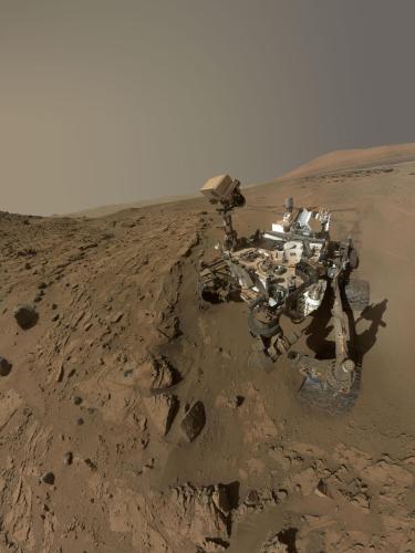 """Curiosity a utilisé l'appareil photo Mahli au bout de son bras en Avril et Mai 2014 pour prendre des dizaines d'images qui ont été combinées dans cet autoportrait. Il est dans la région appelé """"Windjana"""" et on peut y voir le forage et le pré-forage effectués dans la roche (2 ronds gris un peu à gauche du centre de l'image) (Crédit: NASA / JPL-Caltech / MSSS)"""