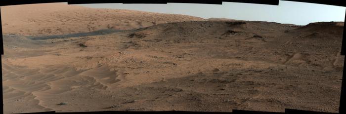 """Cette vue de la caméra MastCam sur le rover Curiosity montre l'affleurement """"Pahrump Hills"""" et le relief environnant vu d'une position à environ 20 mètres au nord-ouest de l'affleurement, le 17 septembre 2014, lors du 751e SOL. La scène comprend quatre régions distinctes:  1) des ondulations de sable au premier plan, du type de celles rencontrées dans le cratère Gale 2) la section Pahrump Hills de la formation Murray, où environ 18 mètres de la roche couches sont exposés 3) une crête plus sombre au loin vers la gauche 4) des pentes au nord-ouest du Mont Sharp à l'arrière-plan, où une transition brutale est apparente entre les buttes et les vallées dans la partie inférieure et les lits inclinés et sculptées dans la partie supérieure partie (Image Credit: NASA/JPL-Caltech/MSSS)"""