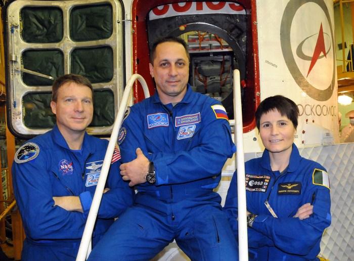 Dans le bâtiment d'intégration au cosmodrome de Baïkonour au Kazakhstan, les membres de l'Expedition 42/43, Terry Virts (à gauche), Anton Shkaplerov (au centre) et Samantha Cristoforetti (à droite) posent pour des photos le 19 novembre devant leur vaisseau Soyouz TMA-15M au cours de leur deuxième et dernière répétition générale de pré-lancement. (Credit NASA/Viktor Ivanov)