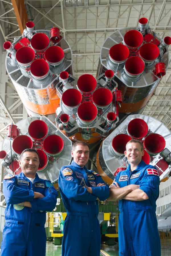 De gauche à droite, Aidyn Aimbetov, Sergueï Volkov et Andreas Mogensen, devant la fusée Soyouz TMA-18M à Baikonour (Credit: Gagarin Cosmonaut Training Center)