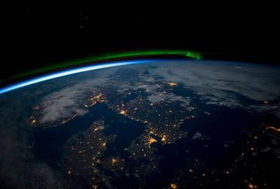 Le sud de la Scandinavie juste avant minuit sous une pleine lune, depuis l'ISS. On peut y voir une aurore boréale verte au nord, la noirceur de la mer Baltique (en bas à droite) (credit NASA).