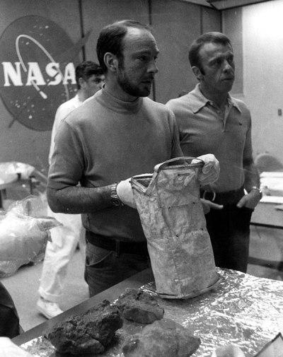 Apollo 14 : Ed Mitchell avec un sac de collecte d'échantillon de roches lunaires lors d'un débriefing post-mission avec des géologues le 18 février 1971. A droite, Stu Roosa. (credit NASA)