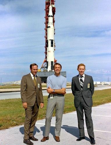 Ed Mitchell (gauche), Al Shepard, et Stu Roosa posant devant leur Saturn V durant le roulage au pas de tir le 9 Novembre 1970 (credit NASA)