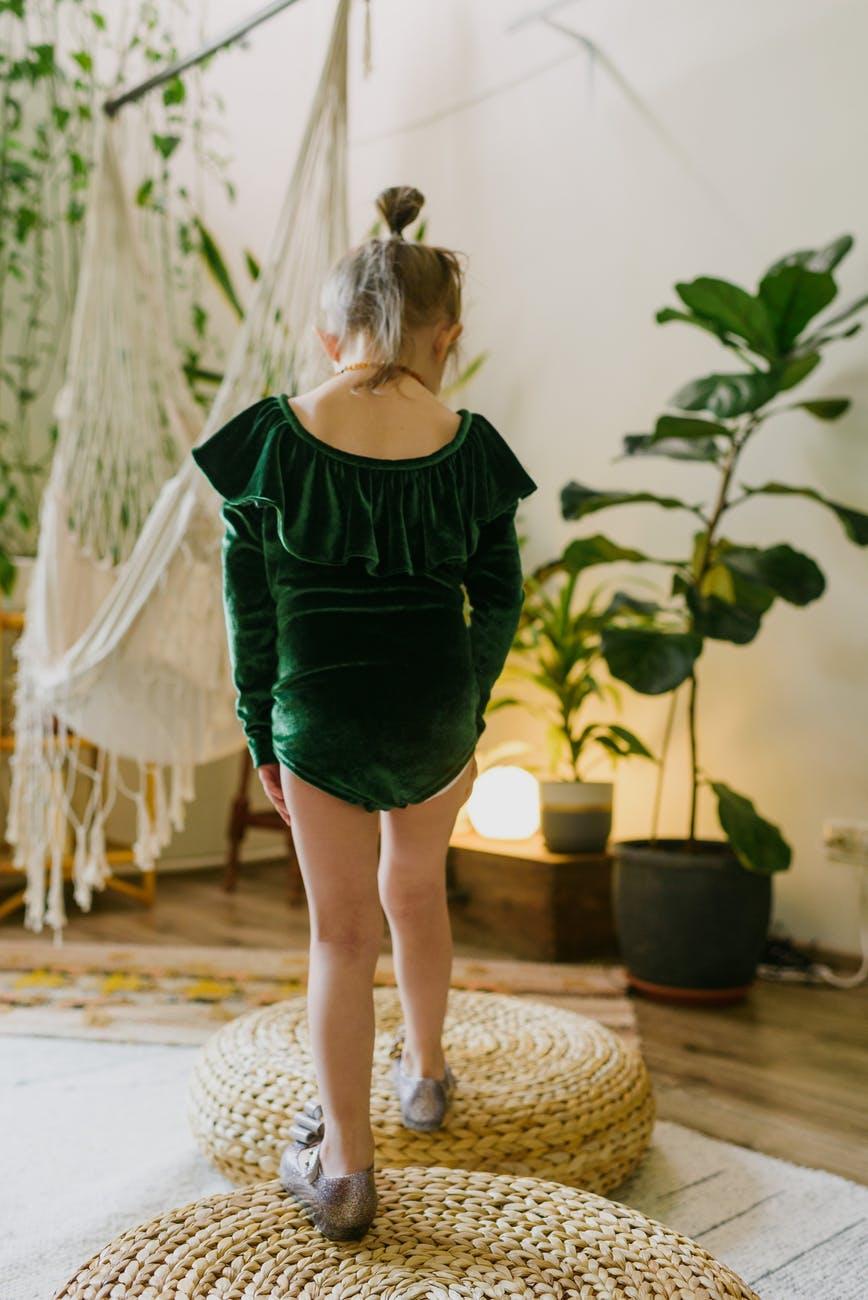 anonymous little kid standing on straw weaker poufs in stylish home