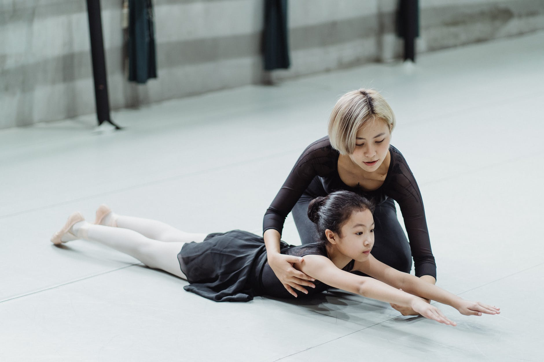 young professional asian ballerina training in studio with adorable little beginner girl