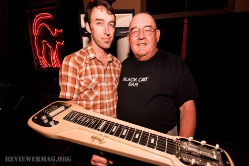 In City Heights at The Black Cat bar with club proprietor Matthew Parker and his father Linton, holding the 1962 slide guitar once owned by Matt's grandfather.