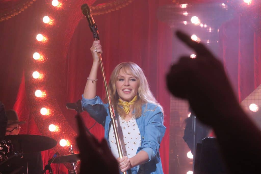 Kylie holds a mic stand