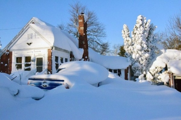 A house and vehicle covered in snow. Image by Novinite.
