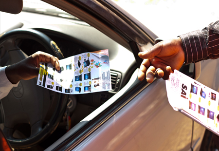 Man handing out a flyer to a motorist at an intersection in Harare. Image credit Mrflyer.co.zw