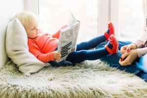 a toddler is sitting by a window reading a big book with an adult off to the side and out of image