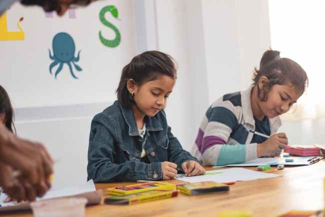 Two girls are sitting at a table with crayons and school supplies working on the paper.