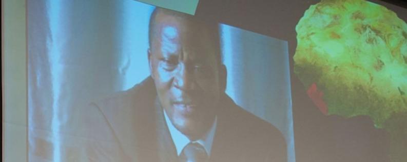 James Golay, presidente de la Unión Misión de África Occidental, habla desde Liberia a una pantalla de video proyectada a cientos de líderes de la iglesia reunidos en la sede central de la denominación. Los líderes oraron por los afectados por la epidemia creciente. Imagen de Viviene Martinelli.