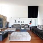 Sobre el piso de madera, los muebles tapizados en terciopelo gris plata armonizan con el blanco de los muros y el gris pizarra de la chimenea.